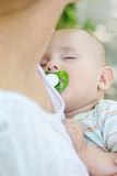 Sleeping baby with a pacifier in mother's Royalty Free Stock Photo