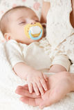 Sleeping baby portrait in mother hand, happy maternity and childhood concept, focus on hand Stock Photography