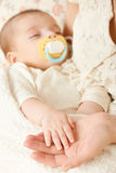 Sleeping baby portrait in mother hand, happy maternity and childhood concept, focus on hand Stock Images