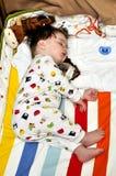 Sleeping baby in pyjamas with dummies nearbly. Sleeping baby in pyjamas with dummies Stock Images
