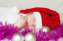Sleeping baby-santa among christmas decoration Stock Images