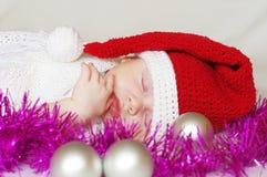 Sleeping baby-santa among christmas decoration Stock Images