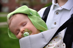 Sleeping Baby on Sling. A baby sleeps in a sling with a pacifier in mouth Stock Photo