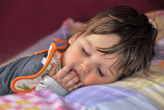 Sleeping baby sucking fingers Stock Photography