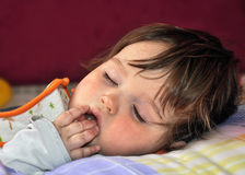 Sleeping baby sucking fingers Stock Photos