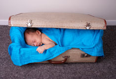 Sleeping baby in suitcase. Cute sleeping baby in an old suitcase and wrapped in a blue blanket Royalty Free Stock Image