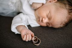 Baby Hand Holding Gold Wedding Ring. Sleeping baby with wedding rings Royalty Free Stock Photos