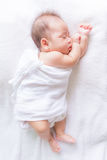Sleeping baby. On white bed Stock Photography
