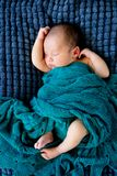 Sleeping Baby wrapped in green wool blanket - arms and legs out. Sleeping Baby Boy wrapped in green wool blanket on dark blue textured blanket with arms and legs Royalty Free Stock Photography