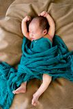 Sleeping Baby wrapped in green wool blanket on beige cushion. With arms and legs stretched out - caucasian and pacific islander ethnicity Royalty Free Stock Photography