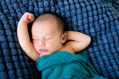 Sleeping Baby  wrapped in green wool blanket on dark blue textur. Sleeping Baby wrapped in green wool blanket on dark blue textured blanket with arms out Royalty Free Stock Images