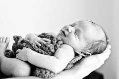 Sleeping Baby wrapped in wool blanket being held in mothers hand. Black and White image of Sleeping Baby Boy wrapped in wool blanket being held in mothers hands Stock Photo