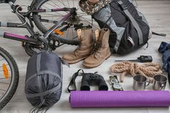 Sleeping bag, bicycle and set of camping equipment. On wooden floor royalty free stock photos