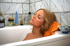 Sleeping in the Bath. A Pretty Girl Relaxes in the Bath early one morning royalty free stock photo