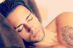 Sleeping beautiful man. Handsome young man happily sleeping in bed stock image