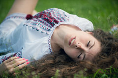 Sleeping Beauty. Portrait of a young sexually girl in the national shirt lying on the grass Stock Images