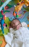 Sleeping Beauty. A three weeks old baby girl sleep surrounded with toys Stock Photo
