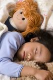 Sleeping Beauty 3. A young girl sleeps with her favorite stuffed animals Stock Photos