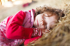 Sleeping Beauty. Beautifully sleeping little girl smiling calmly in hay Royalty Free Stock Images
