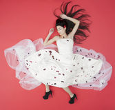 Lying beauty bride in white dress isolated on red Stock Image