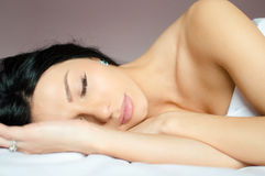 Sleeping beauty: closeup portrait of beautiful brunette young woman in sleep on white bed Royalty Free Stock Image