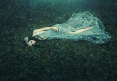 Sleeping Beauty. The girl lies on the grass in a dark, dense forest. An unusual transparent dress. Artistic processing stock images