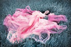 Sleeping beauty on the grass pink dress. Sleeping beauty young woman from fairy tale laying on silver grass royalty free stock photos