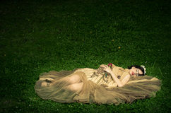 The sleeping beauty lays on the grass Royalty Free Stock Image