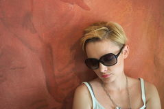 Beautiful blond woman sitting at the wall Royalty Free Stock Photos