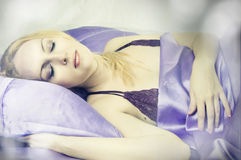 Sleeping beauty woman in silk Bed alone closeup. In morning Royalty Free Stock Photos