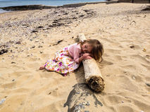 Sleeping Beauty. A young girl sleeping on a log at the beach Royalty Free Stock Images