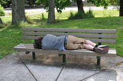 Sleeping on a bench in a public