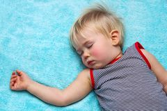 Sleeping blond haired child on blue royalty free stock photography