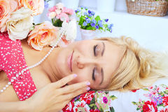 Sleeping blond woman lying on pillow among flowers Stock Photo