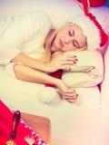 Sleeping blonde woman in santa hat Royalty Free Stock Image