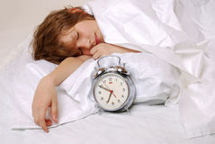 Sleeping boy. Boy sleeps in bed, alarm clock in front Royalty Free Stock Images
