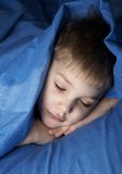 Sleeping boy. In blue bedclothes royalty free stock photography