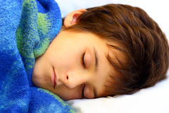 A sleeping boy. With blue blanket on a white pillow close up Stock Images