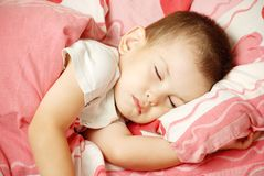 The sleeping boy. Carefree sleeping little boy on a bed Royalty Free Stock Photo