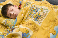 Sleeping boy. The Image of the boy sleeping on yellow bed-clothes Royalty Free Stock Image
