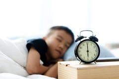 Sleeping boy and alarm clock Royalty Free Stock Photos