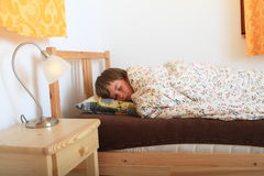 Sleeping boy. Boy sleeping in a bed on pillow under blanket with flowers with a lighting lamp on bedside table Royalty Free Stock Image