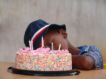 Sleeping boy by birthday cake Stock Photo