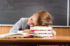 Sleeping boy with books at the desk Royalty Free Stock Photo