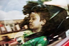 Sleeping boy in car seat. Young boy sleeping in car seat with safety belt, seen through the window Stock Photo