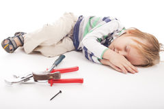 Sleeping boy with hammer and pliers Royalty Free Stock Images