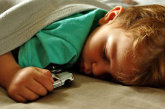 Sleeping boy. Little boy placidly sleeps with a toy car in his hand stock photo