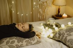 Sleeping  boy lying in bed evening in dark against the backgroun. D of lanterns Stock Photography