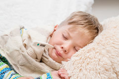 Sleeping boy lying in bed with a thermometer in mouth Royalty Free Stock Images