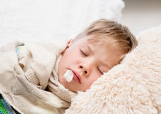 Sleeping boy lying in bed with a thermometer in mouth Royalty Free Stock Photo